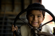 Young boy holding a steering wheel