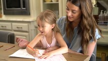 a mother coloring with her daughter