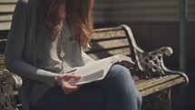woman reading a Bible sitting on a park bench