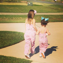 cousins in matching outfits walking holding hands