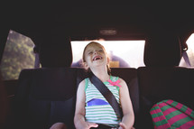 a girl laughing in the backseat