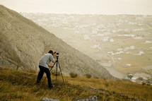 A man snaps a photo using a tripod on a hillside.
