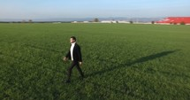man walking through a field in a suit