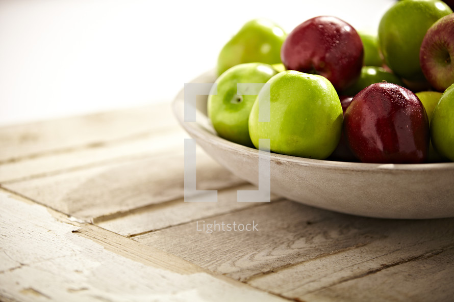 A group of green and red apples sit in a bowl