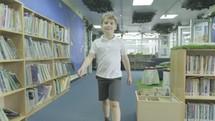 a boy walking through the library of a school
