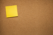 sticky note on a cork board