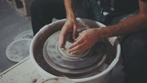 a man molding clay on a potter's wheel