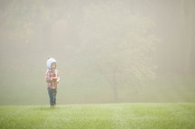 a girl standing outdoors in the fog