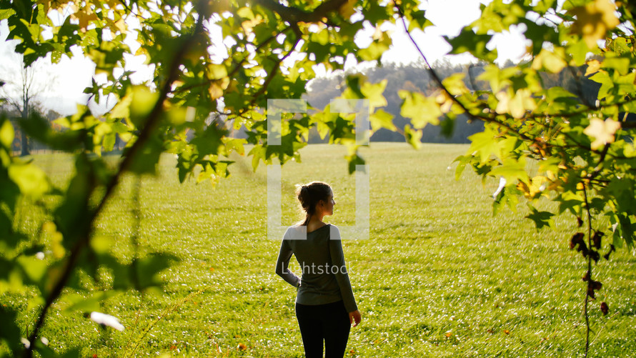 woman standing in a field of cut grass