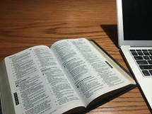 laptop computer and Bible on a desk