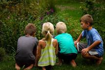 kids watching creatures in a flower garden