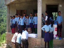school children in Nepal carrying supplies down a dirt road