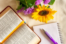 opened Bible, pen, notepad, and flowers
