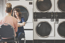 women in talking at a laundromat