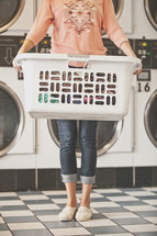 a woman holding a basket full of laundry at a laundromat