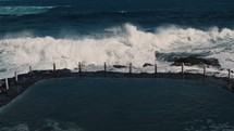 Big wave crashing over the break wall.