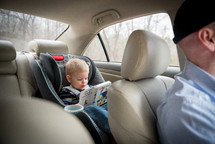 toddler boy reading a book in a carseat