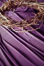 Crown of thorns on purple drape.
