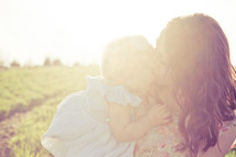mother kissing daughter with sun flare