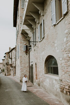 a nun walking on a narrow street
