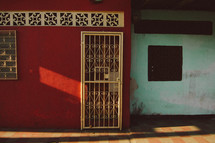 barred doors and windows on a red house