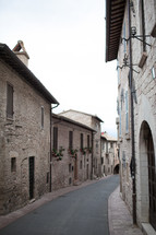 An alley between rows of old stone buildings.
