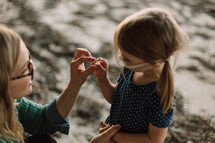 a girl showing her mother a seashell