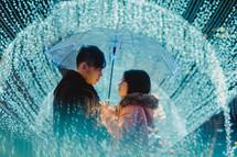 a couple standing under blue lights and an umbrella