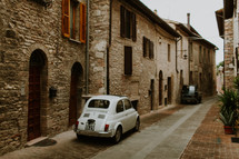 Two small cars parked in a narrow alleyway between old stone buildings.