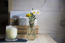 daisies in a vase and candle