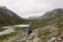 a woman running up a mountainside in Norway