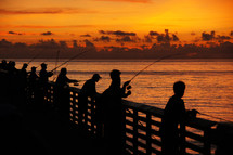 Silhouettes of men fishing off of a pier at dawn