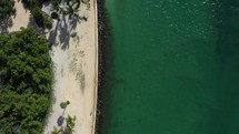 Top-down (Bird's eye) view of sandy beach shoreline, water, and lighthouse