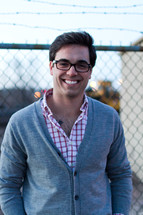 smiling man in glasses standing in front of a chain linked fence