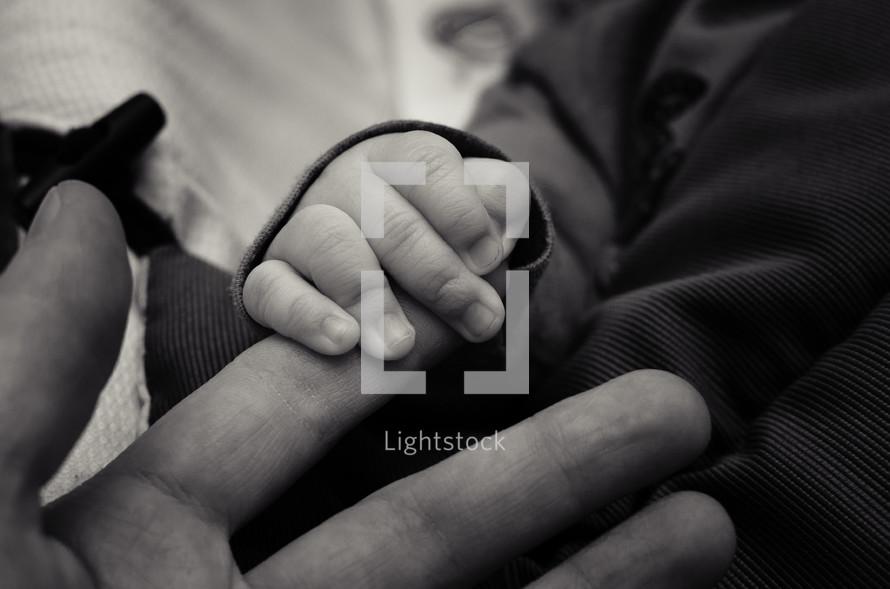 infant holding man's fingers