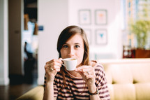 A woman sits on a couch drinking coffee from a white coffee cup.