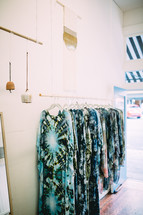 Tie dyed garments hanging against a white wall.