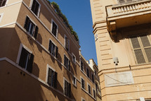 windows on the sides of buildings lining the narrow streets of Rome