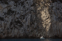 boat in front of a cliff in Italy