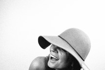woman in a hat laughing