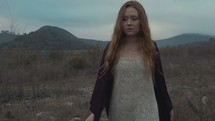 woman walking through grasslands