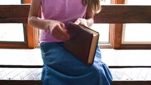 a girl sitting reading a Bible