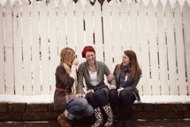 teen girls giggling in front of a white fence