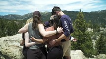 people in a prayer circle on a mountaintop