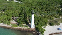 Aerial Fly Over a Beach Lighthouse and dense trees