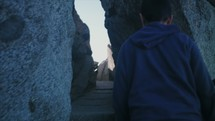 Person walking up mountain through narrow passageway.