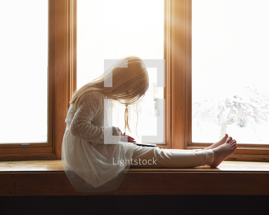 a child with a tablet sitting in a window