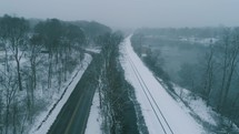 aerial view over a winter road and train tracks