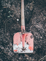 A red shovel  sitting on some dirt ready to be dug