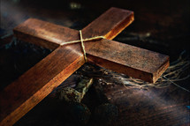 a wood cross, crown of thorns, and three rusty nails